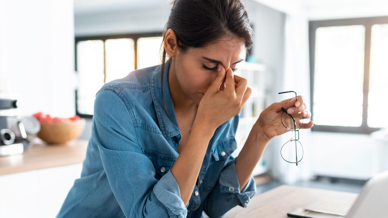 Stress und Entspannung: Frau reibt sich erschöpft die Stirn.
