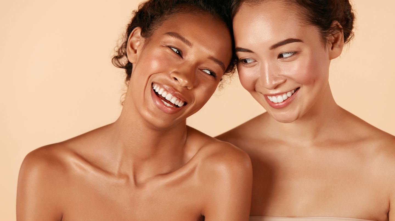 Typgerechte Hautpflege: Zwei junge, lächelnde Frauen mit glatter Haut und freien Schultern legen die Köpfe aneinander.