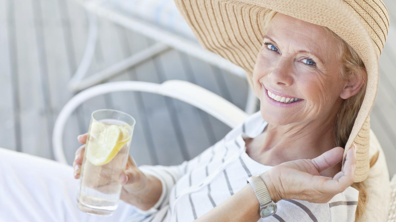 Aktinische Keratose: Ältere lächelnde Frau mit Sonnenhut und Wassergla in der Hand sitzt im Stuhl auf der Terrasse